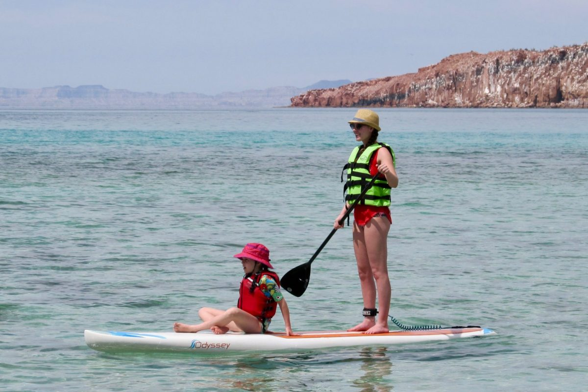 Two kids stand-up paddle-boarding during 2018 Family Adventure Week at the CSU Todos Santos Center.during 2018 Family Adventure Week at the CSU Todos Santos Center.