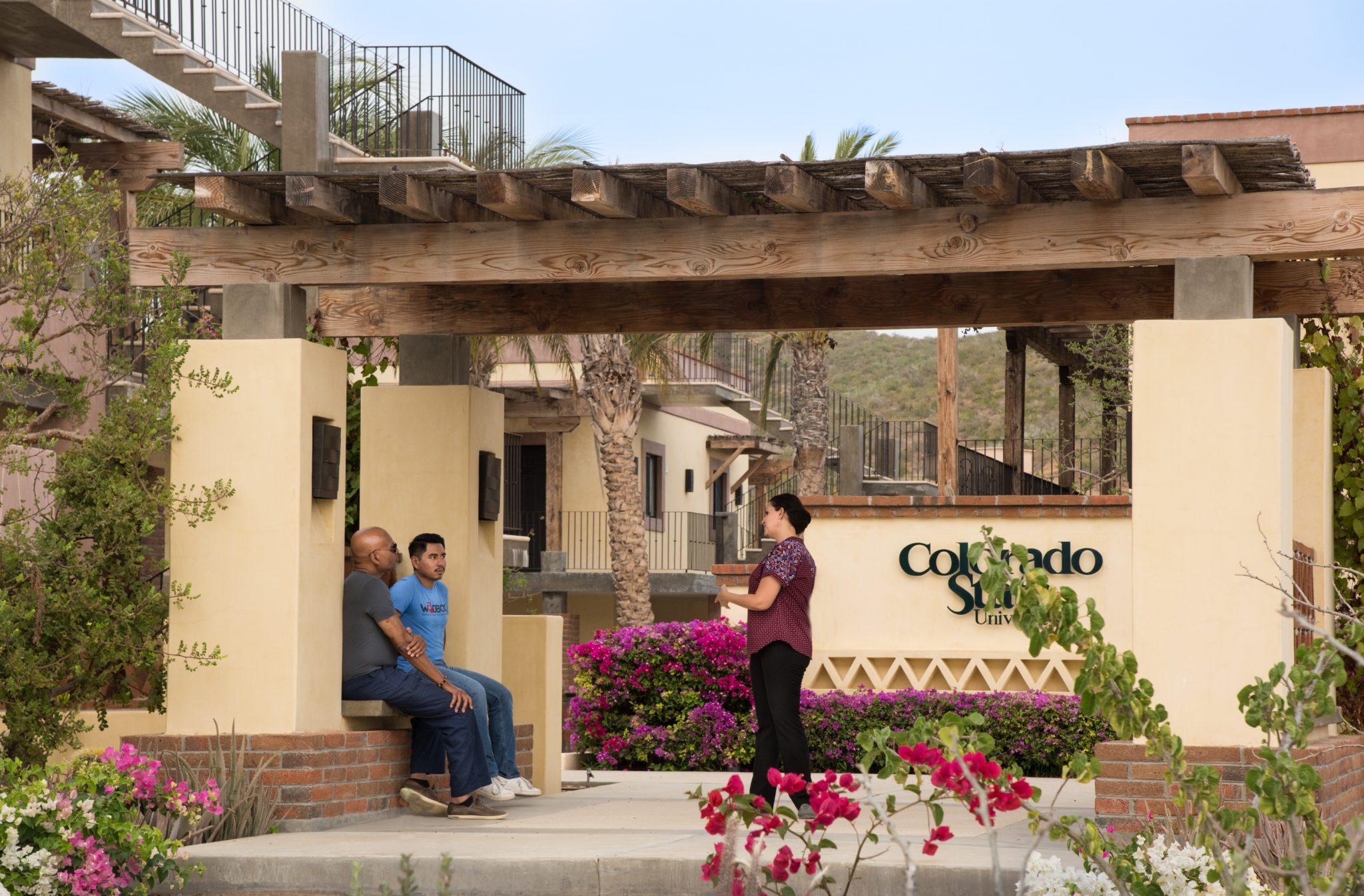 CSU Todos Santos Center staff converse under outdoor pergola.